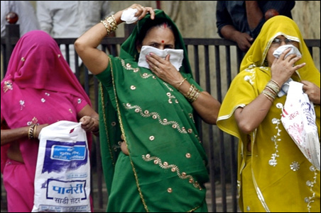 Women cover their faces with handkerchiefs as they walk outside a special ward for H1N1 influenza testing at the Kasturba Hospital in Mumbai, Aug. 9, 2009.
