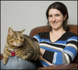 A cat with a heart dangling from its collar sits on a woman's lap.