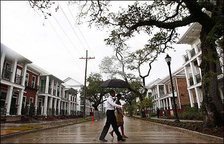 President Barack Obama and first lady Michelle Obama cross the street in the Columbia Parc Development to visit newly built homes in New Orleans on Sunday.
