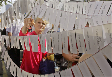 A woman reads the names of persons missing since the wars in the former Yugoslavia, written on leaflets and placed in front of Croatian embassy in Belgrade Aug. 30, 2005, in connection to the International Day of Missing People.