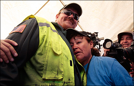 Elizabeth Segovia, sister of one of the 33 trapped miners, is comforted by drilling machine operator Jeff Heart after the completion of the escape hole.