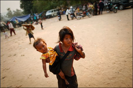 Displaced Cambodians carry their belongings after fleeing from the area near the border between Thailand and Cambodia.