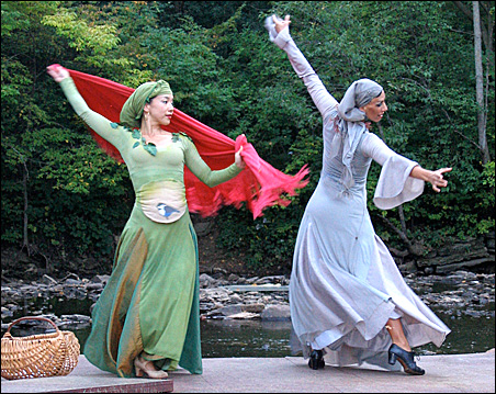 Trickling waters form a backdrop for dancers.