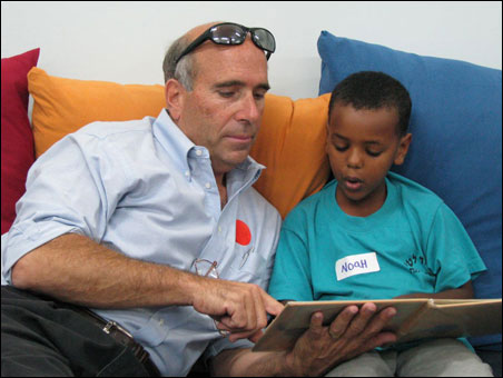 Minnetonka resident Bruce Goldstein, who has hosted PACT Hadera participants, listens as Noah, a student in PACT's Alternative Learning Space program in the Givat Olga school, reads a Hebrew book about a dog and a cat.