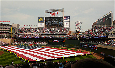 Before the game, stadium construction workers carried the American flag onto the field.