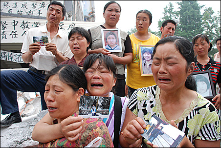 Weeping parents hold portraits of their children during a May 27 memorial service at the ruins of Juyuan Middle School.