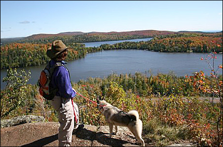 Jetty St. John and his dog Scarlett overlooking Cook County's rugged landscape which poses impediments to connectivity.