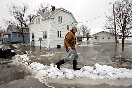 Justin Thompson walks on a leaking, frozen sandbag dike