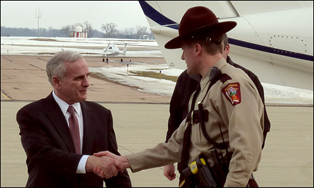 Gov. Mark Dayton greets a state trooper at the Mankato airport terminal during a tour of the state in February touting his budget proposal.