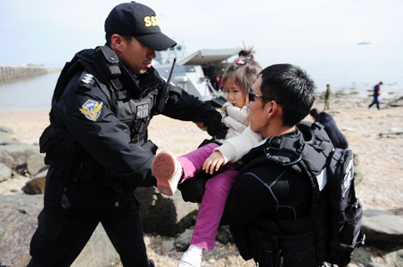 Members of South Korean Coast Guard evacuate a girl from Yeonpyeong Island after an artillery attack by North Korea.