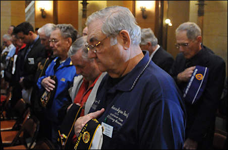 Roger Ball, center, one of about 120 Veterans Day on the Hill attendees, recites the Pledge of Allegiance.