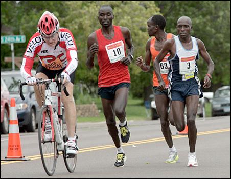 Kenyan runner Philemon Kemboi, 36, left, makes his break and passes, #63 Chris Kipyego of Kenya, and #3 David Rutoh of Kenya. Kemboi won with a time of 2 hours, 15 minutes, 44 seconds.