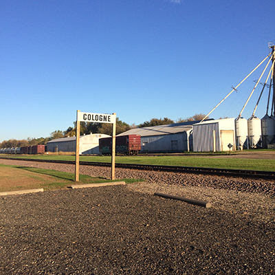 photo of cologne railroad sign with grain silo in background