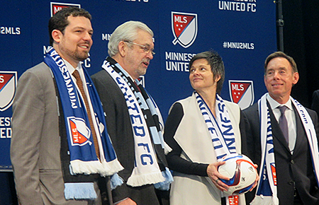 soccer owners in mn united regalia at podium