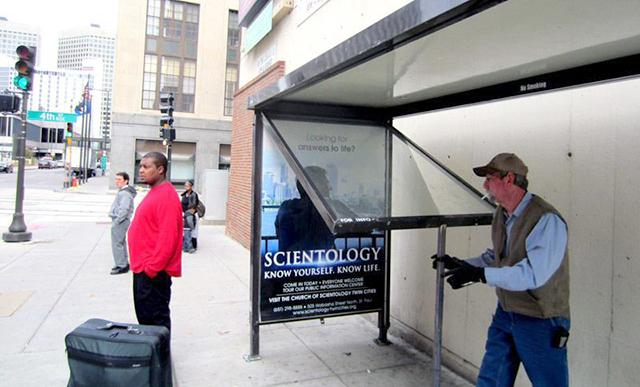 An employee of CBS changing a bus stop advertisement in downtown St. Paul.