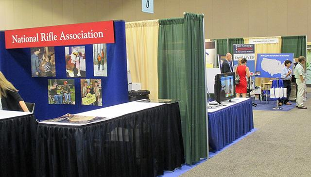NRA and Brady Campaign to Prevent Gun Violence booths on the floor.