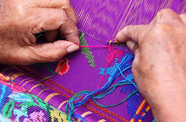 A craftswoman embroidering a shawl outside the ruins of Quirigua, Guatemala.