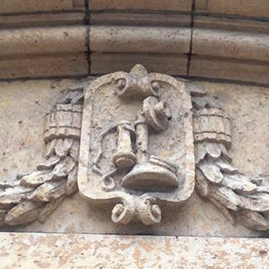 Carved into stone over the front entrance is a candlestick-style telephone