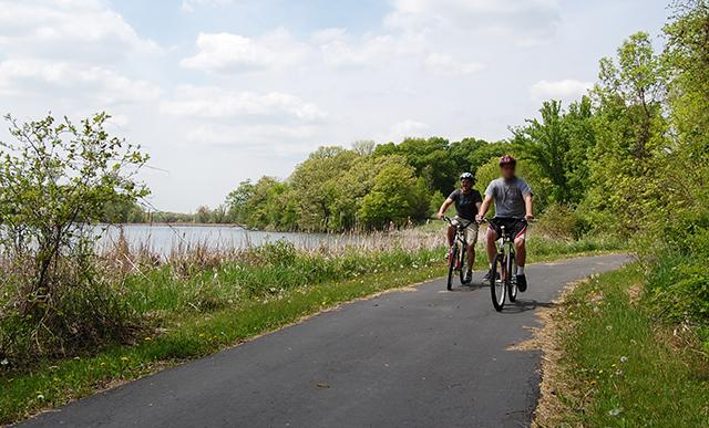 A Vinland staff member biking with a client along a lakeside trail.