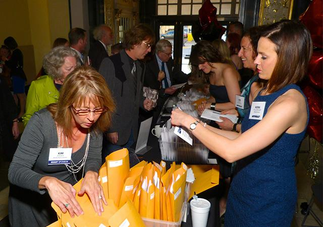 MinnRoast co-chair Kim Kieves, left, assisting with sponsors' packets