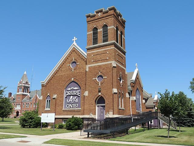 photo of a church building with a sign for the prairie arts center on it
