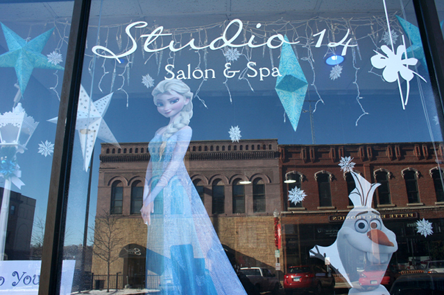 """Historic buildings are reflected in the windows of Studio 14 Salon and Spa at 204 Central Avenue North. The salon created a """"Frozen"""" display for a downtown holiday decorating contest."""