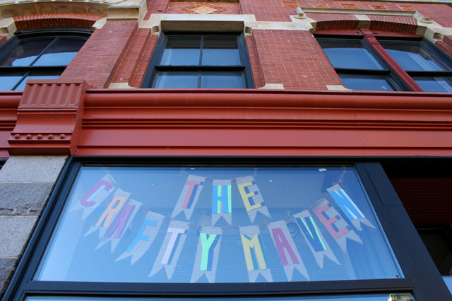 Crafty signage suspended high in a window at The Crafty Maven hints at the crafty goodness you will find inside this historic building at
