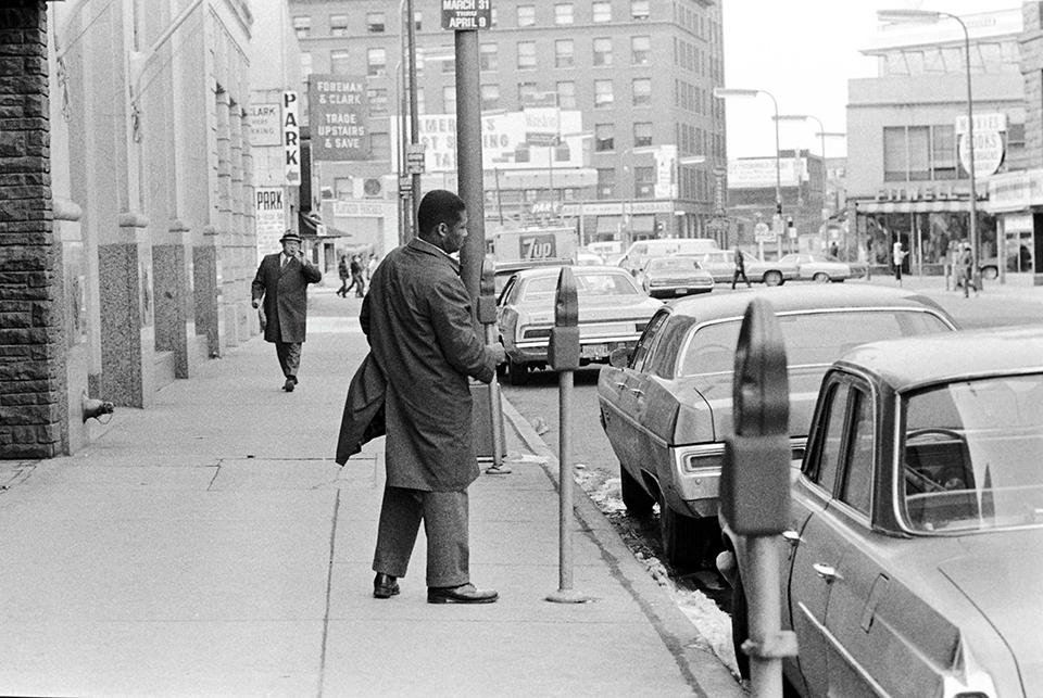 photo of man putting change in parking meter