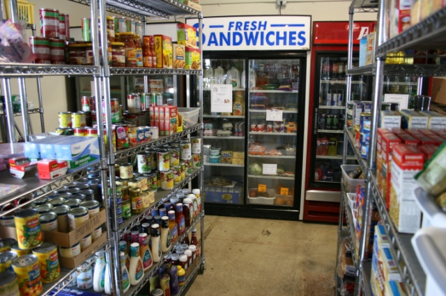 The grocery section of the store includes basic perishables like dairy products, some fruit, lettuce and more. Canned, boxed and bagged foods, personal care items, and miscellaneous items like greeting cards, tape and such fill eight shelving units.