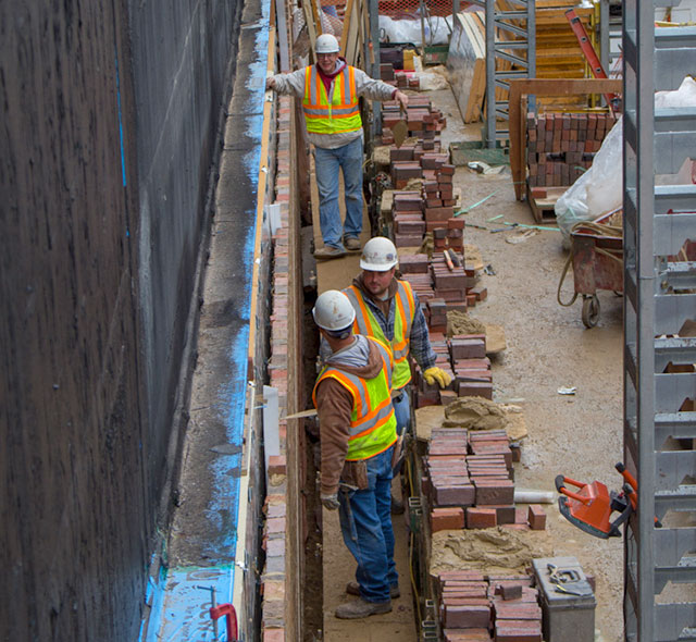 Bricklayers install the specially-made waterstruck bricks